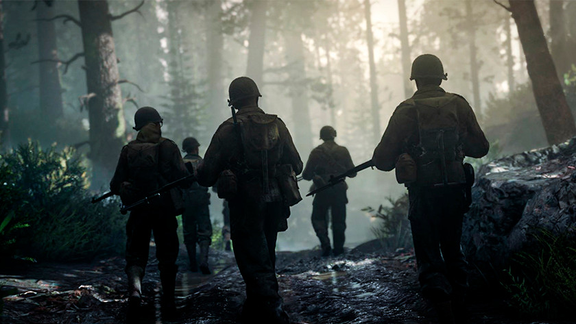 American soldiers from a World War II game walk through a forest.