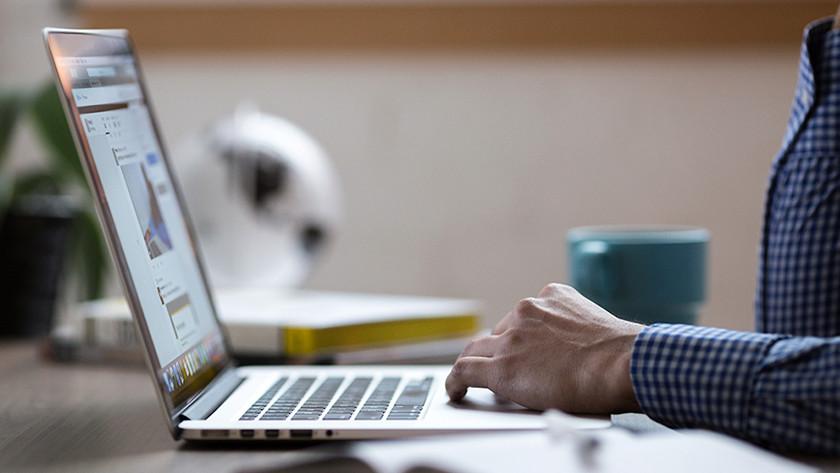 Une main sur le clavier de l'ordinateur portable.