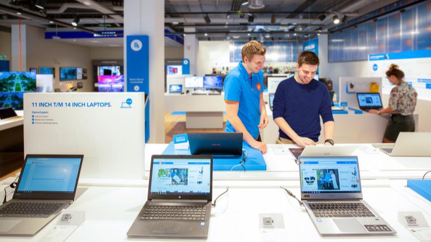 Man bekijkt laptops in Coolblue winkel en Coolblue medewerker helpt hem.