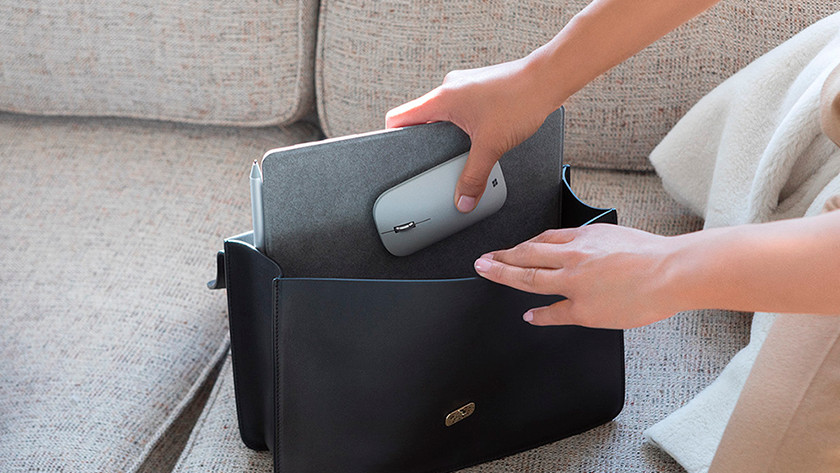 Woman puts a 10-inch laptop in a handbag with a mouse.
