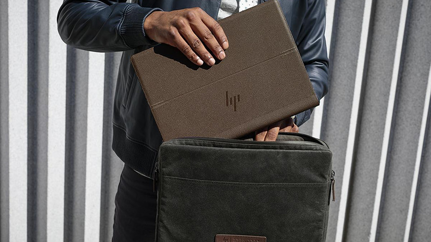 Man puts HP Spectre Folio in a leather bag.