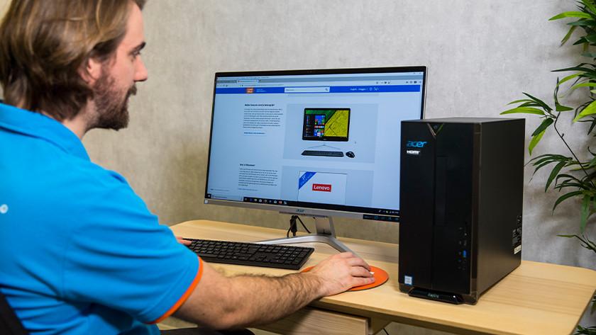 Man works on desktop PC.
