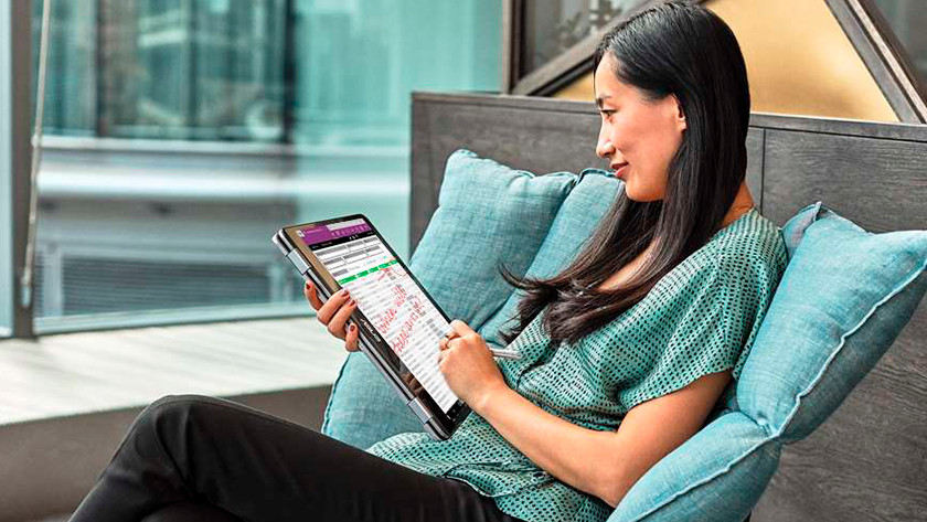 Woman draws on the screen of a 2-in-1 laptop with a stylus and Windows ink