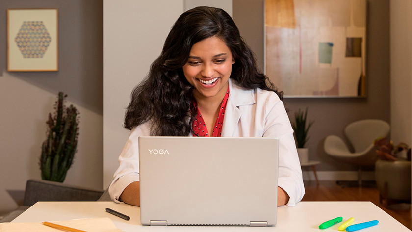 Woman laughs at what she sees on a Yoga laptop.