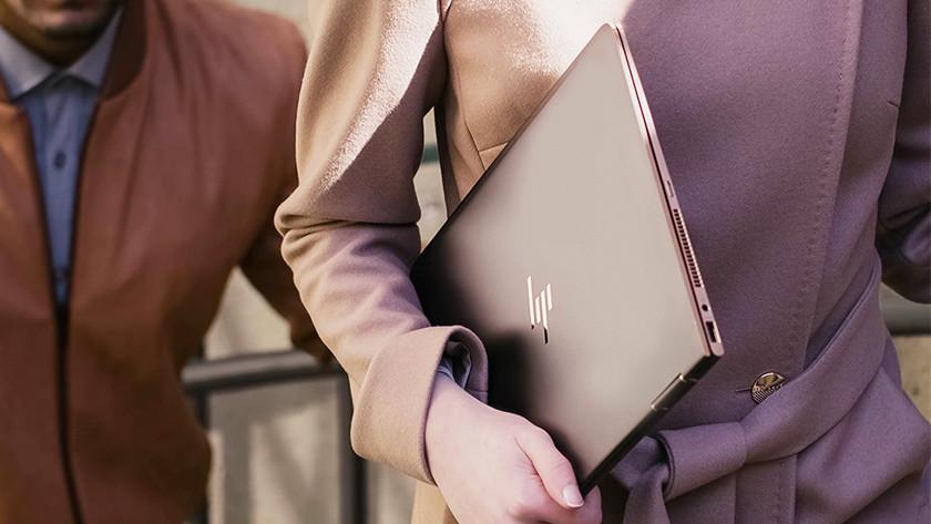 Une femme a un ordinateur portable HP sous le bras.