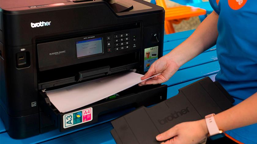 Vrouw haalt papier uit printer