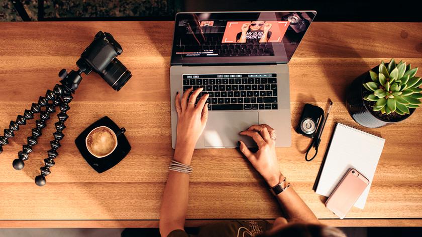 Une femme édite une vidéo sur MacBook derrière son bureau. Une caméra est sur le bureau.