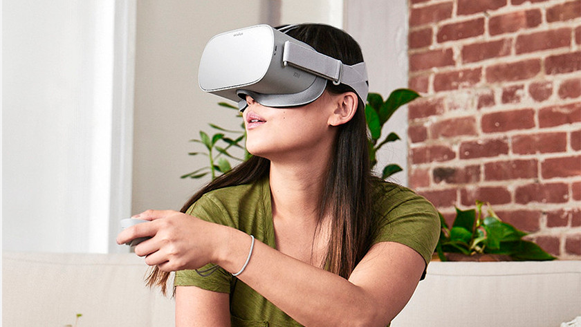Woman with virtual reality gear on head and VR controller in hand.