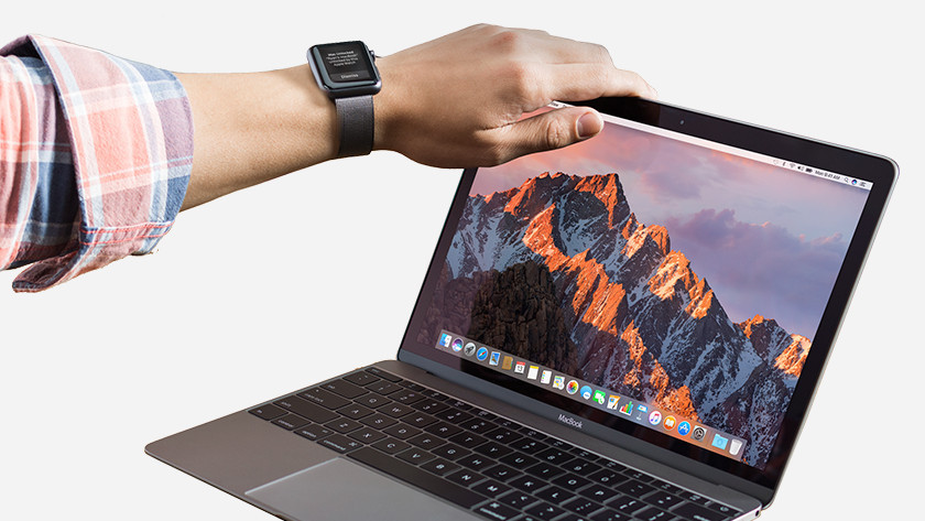 Hand on screen of MacBook Pro.