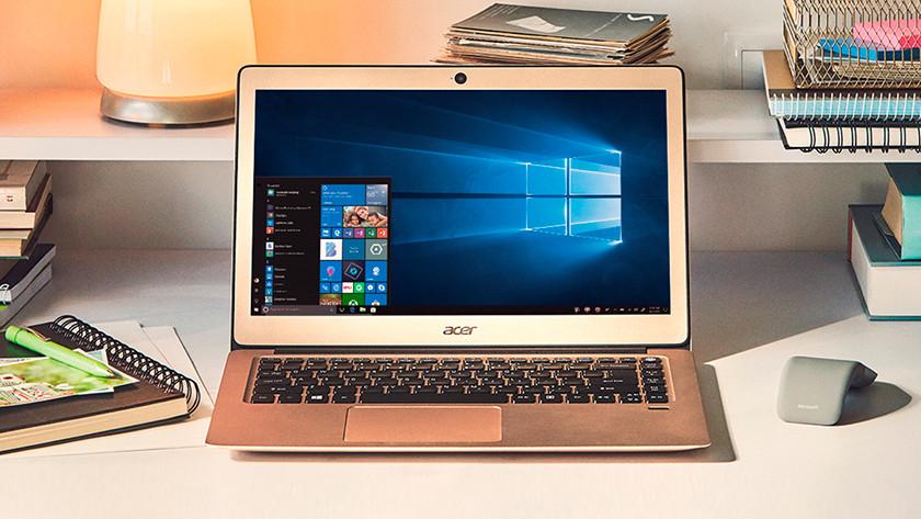 Acer laptop on desk in room.