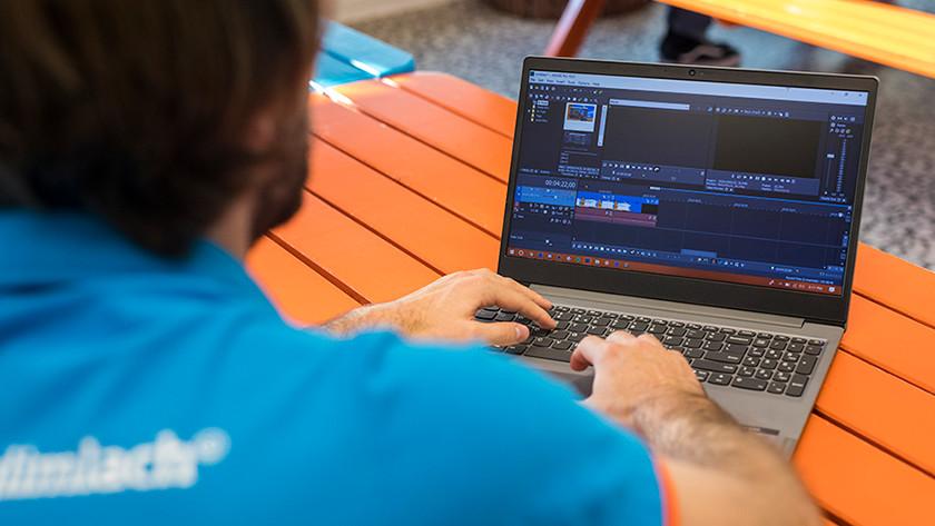 Man bewerkt video's op laptop.