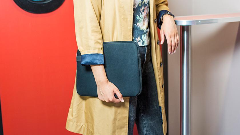 Vrouw in trein houdt laptopsleeve vast.