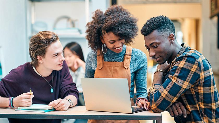 Drie scholieren werken samen achter laptop.