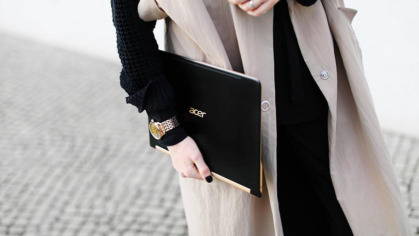 Une femme prend un ordinateur portable Swift 7 sous le bras.