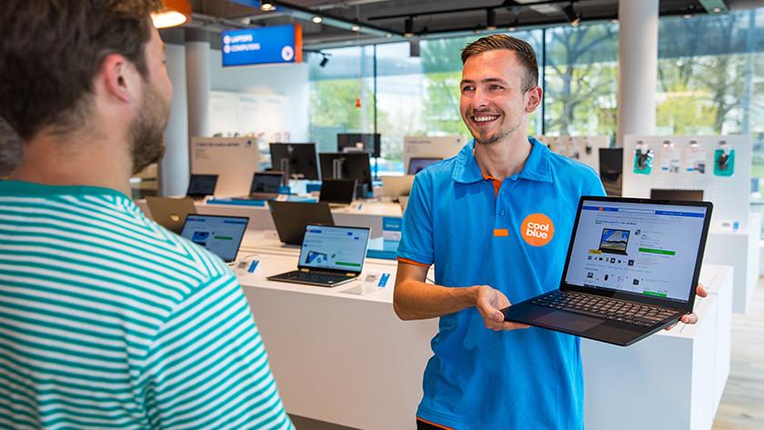 Coolblue medewerker toont laptop in winkel aan klant.