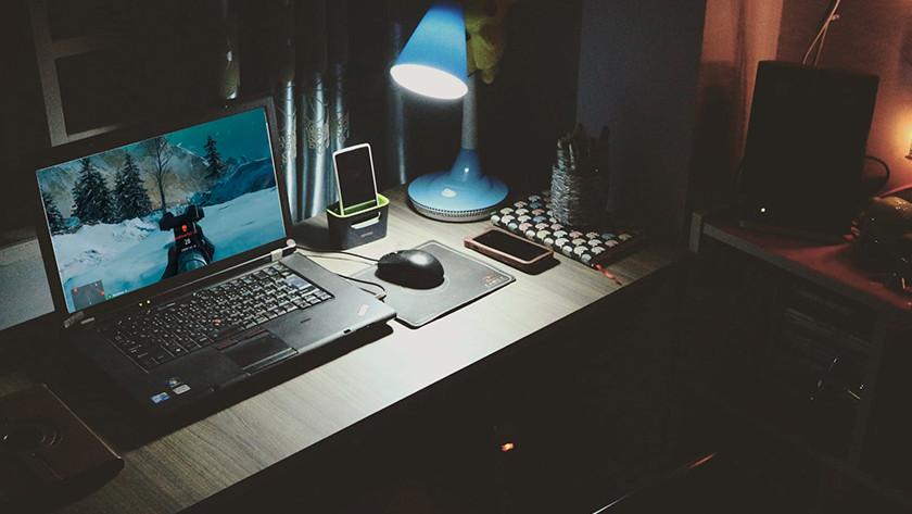 Gamen op laptop in donkere slaapkamer.