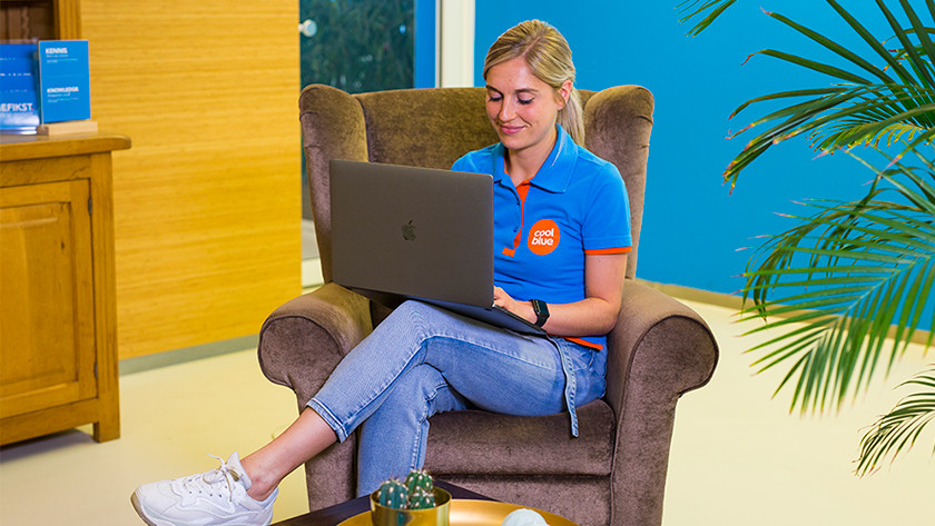 Girl works behind MacBook Pro on lounge chair.