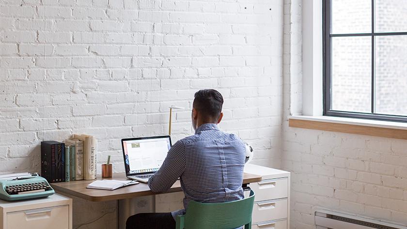 Man werkt achter bureau op zijn laptop met uitzicht op een muur.