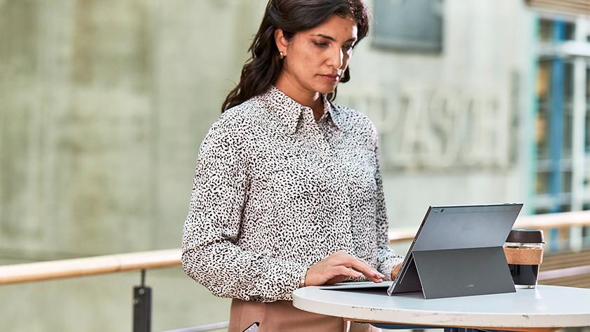 Een zakenvrouw werkt op een Surface laptop.