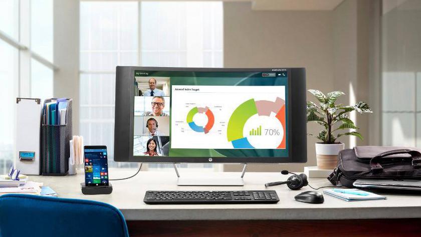 Computer op een bureau met accessoires eromheen.