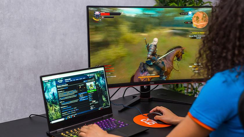 Jouer à Witcher 3 sur un ordinateur portable gamer et un écran PC gamer.