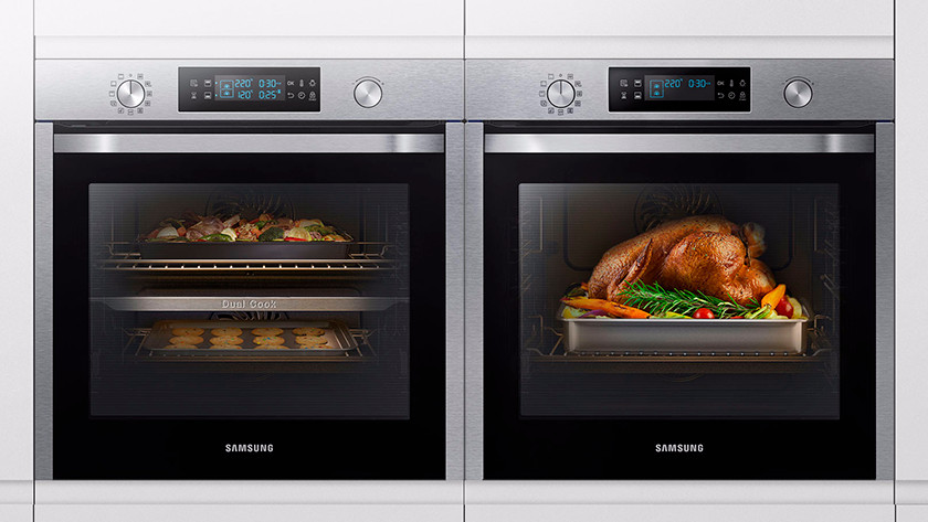 2 ovens with potatoes, chicken, and vegetables