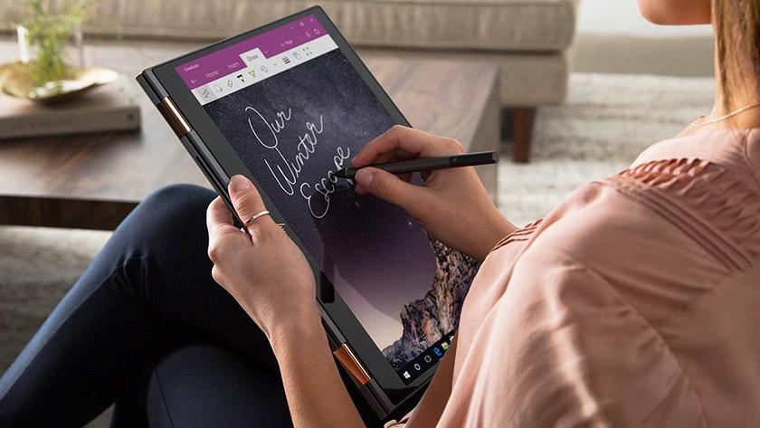 Une femme écrit avec un stylet sur un ordinateur portable à écran tactile en mode tablette.